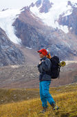Woman with backpack in high mountain — Stock Photo