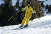 Yellow skier on ski slope — Stock Photo