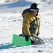 Snowboarder sits on slope in expectation of - Stock Photo