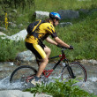 Mountain biker and creek — Stock Photo