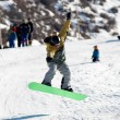 Stock Photo: Flying Snowboarder on green board