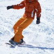 Stock Photo: Orange snowboard girl downhill