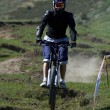 Stock Photo: Fly biker on downhill race