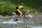 Mountain biker and creek — Stock Photo