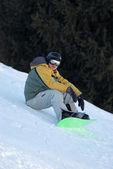Snowboard man sits on ski slope — Stok fotoğraf