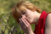 Young woman sniffs wildflower — Stock Photo