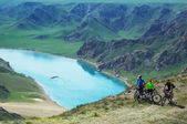 Adventure mountain biking on riverside — 图库照片