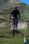 Fly biker on downhill race — Stock Photo