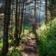Woman on trail in woods — Stock Photo