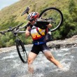 Biker goes over mountain river — Stock Photo