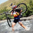 Stock Photo: Biker goes over mountain river