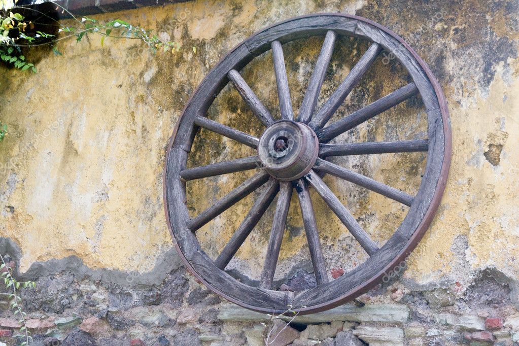 An old wagon wheel leans against a colorfully mottled stucco wall  Stock Photo #2876265