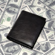 Black wallet on US dollars background — Stock Photo