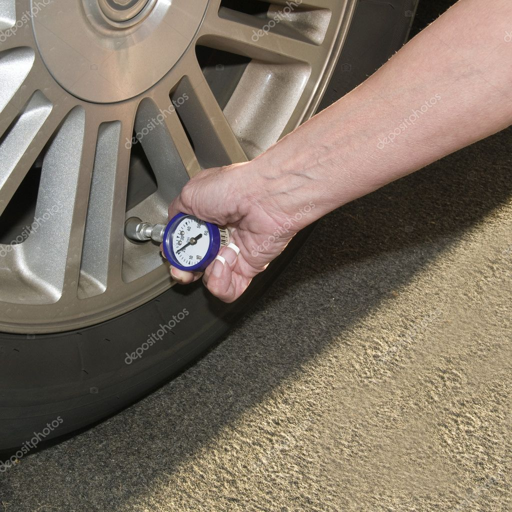 Woman checking her tire pressure to help increase her  gas mileage gauge indicates low pressure — Stock Photo #2705793