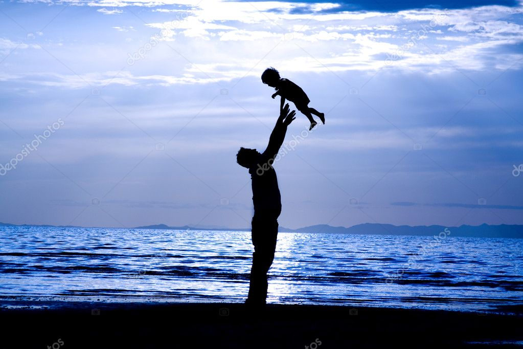 Father throwing his kid up in the air on the beach — Stock Photo #2903731