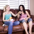 Stock Photo: Two Girls Sitting on SofWatching Movie