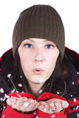 Woman blowing soft white flakes — Stock Photo