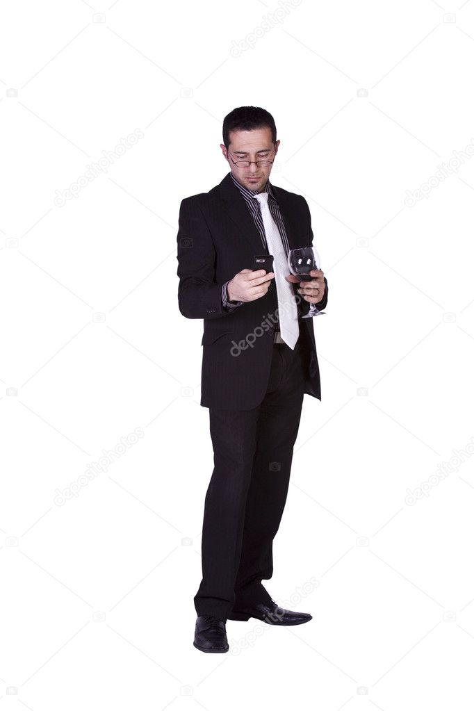 Isolated businessman celebrating with a glass of drink while texting on his cell phone  Stock Photo #3787134