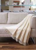 Cream throw draped over a settee — Stock Photo