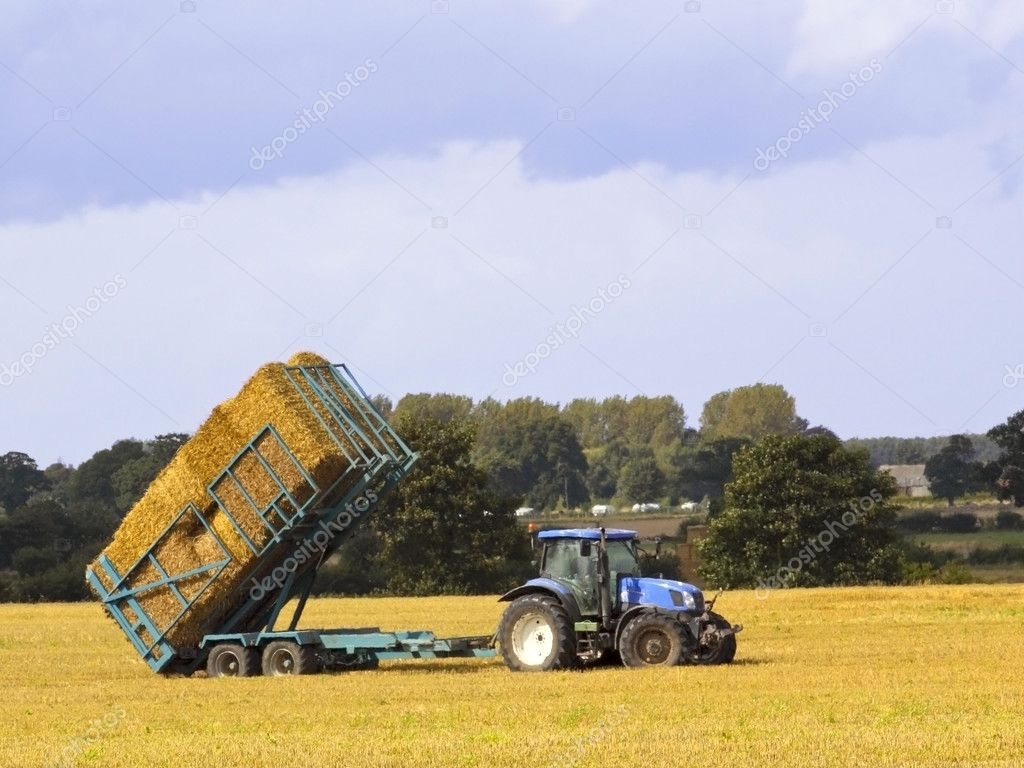 A tractor collecting straw bales in summer — Stock Photo #2767274