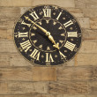 Stock Photo: Old gilded clock on stone wall