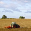 A tractor cultivating — Stock Photo
