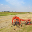 Landscape with hay turning equipment - Stock Photo