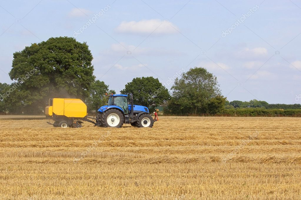 A blue tractor with a yellow baling machine in a stubble field with oak trees and hedgerows — Stock Photo #3668511