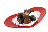 Heart shaped plate of chocolate candy — Stock Photo