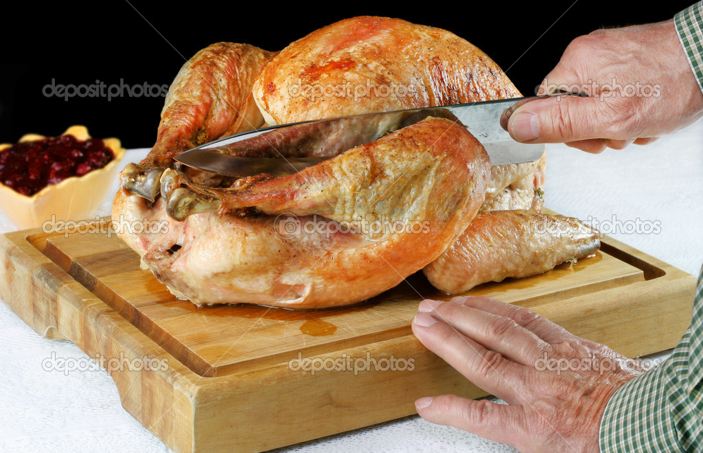 Roast turkey on a cutting board with hands and knife cutting into the leg.  Black background with copy space.  Stock Photo #2807813