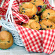 Fresh baked chocolate chip muffins in a basket. - Zdjcie stockowe