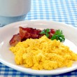 Scrambled eggs and bacon - Stock Photo