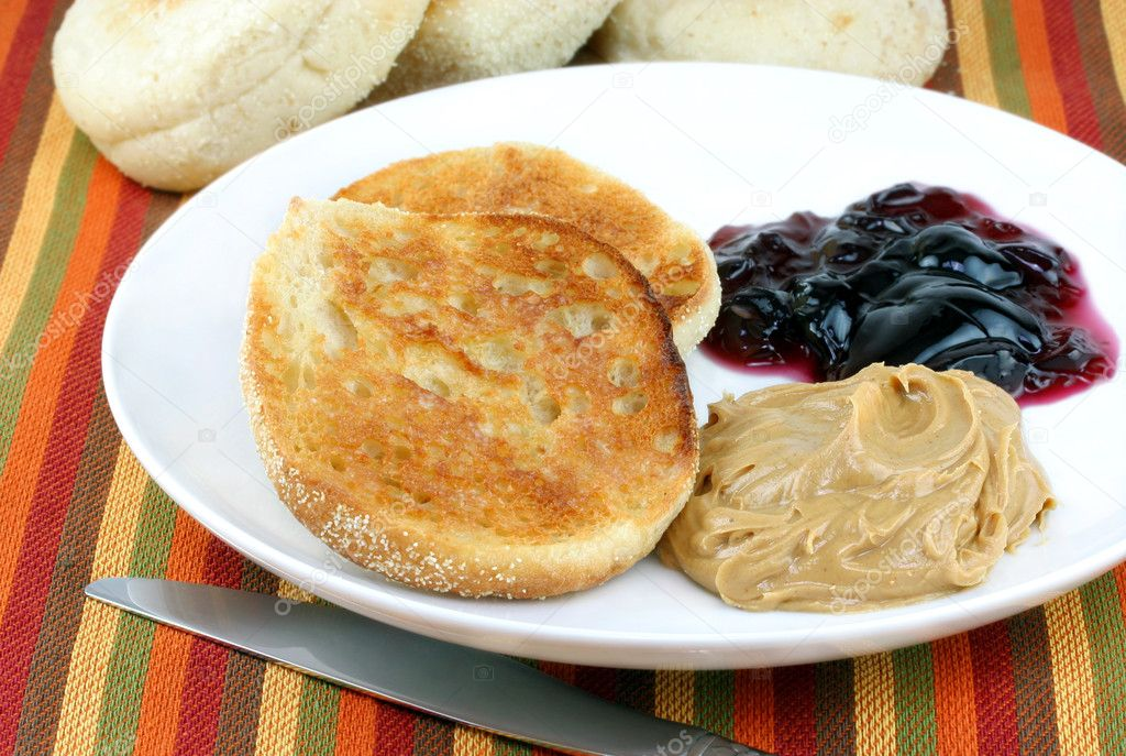 An English muffin on a white plate with peanut butter and jelly to the side.  More muffins in the background.  Stock Photo #2822754