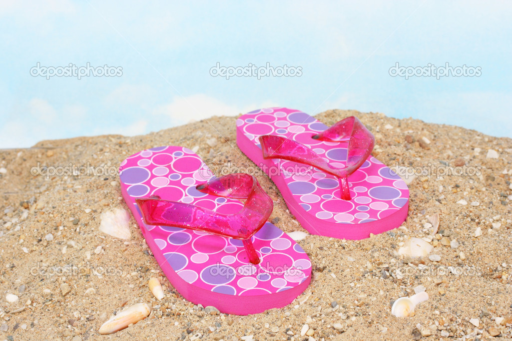 Pretty, feminine pink flip flops on a sandy, seashell beach.  Stock Photo #2823744