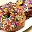 Colorful sprinkled doughnuts. - Foto Stock