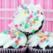 Party cupcakes in front of gift — Stock Photo