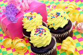Yellow frosted cupcakes with birthday gift — Stock Photo