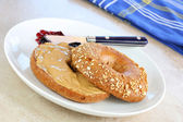 Healthy oat bagel and peanut butter. — Stock Photo