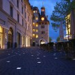 Geneva, Switzerland, one of the city streets at night with glowing paving b - Stock Photo