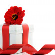 Present with red ribbon and flower — Stock Photo