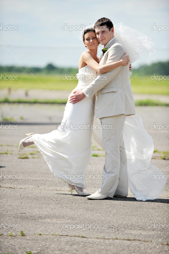 Groom and the bride in a white dress dance on an airfield  Stock Photo #3779650