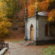 Chapel in autumn forest - Stock Photo