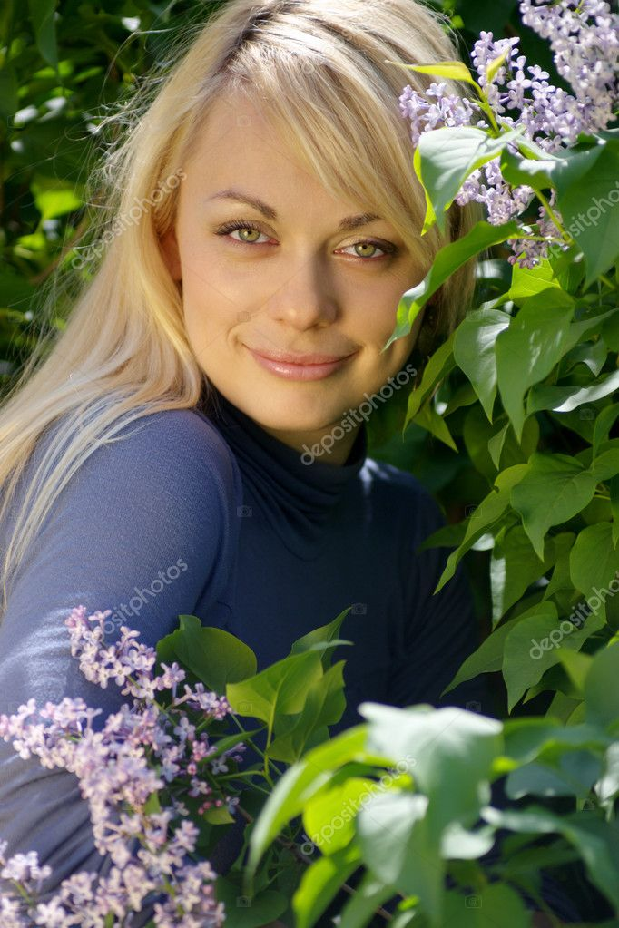 Beautiful young blond woman in blossoming lilacs.  Stock Photo #2710361