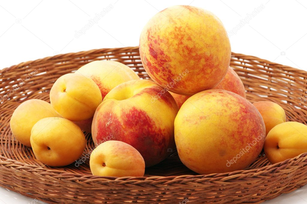 Heap of peaches and apricots in wicker tray on white background. — Stock Photo #2781001
