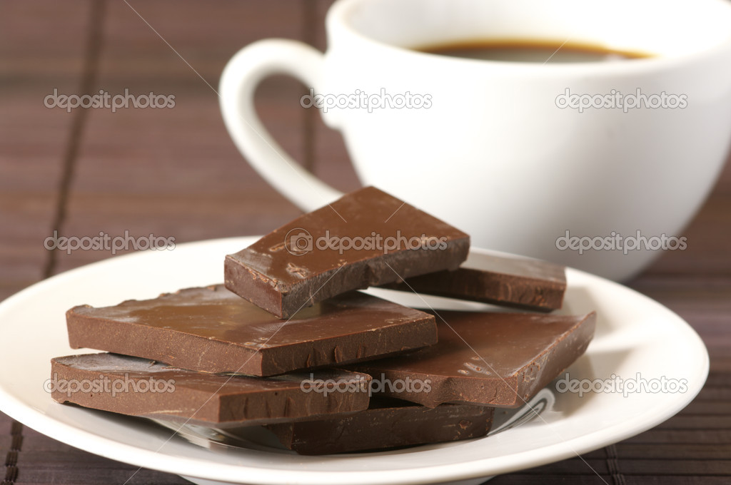 Dark chocolate close-up on white plate and white cup of coffee on brown background. — Stock Photo #2803258