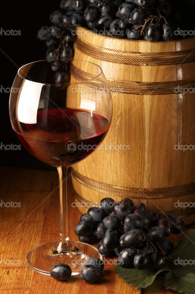 Glass of red wine, dark grape and souvenir barrel on wooden surface. — Stock Photo #2847384