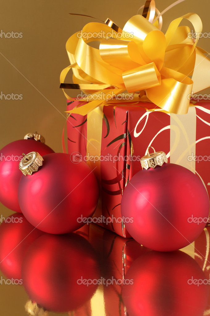 Red Christmas tree decorations and red/gold gift on golden background.  Stock Photo #2847864