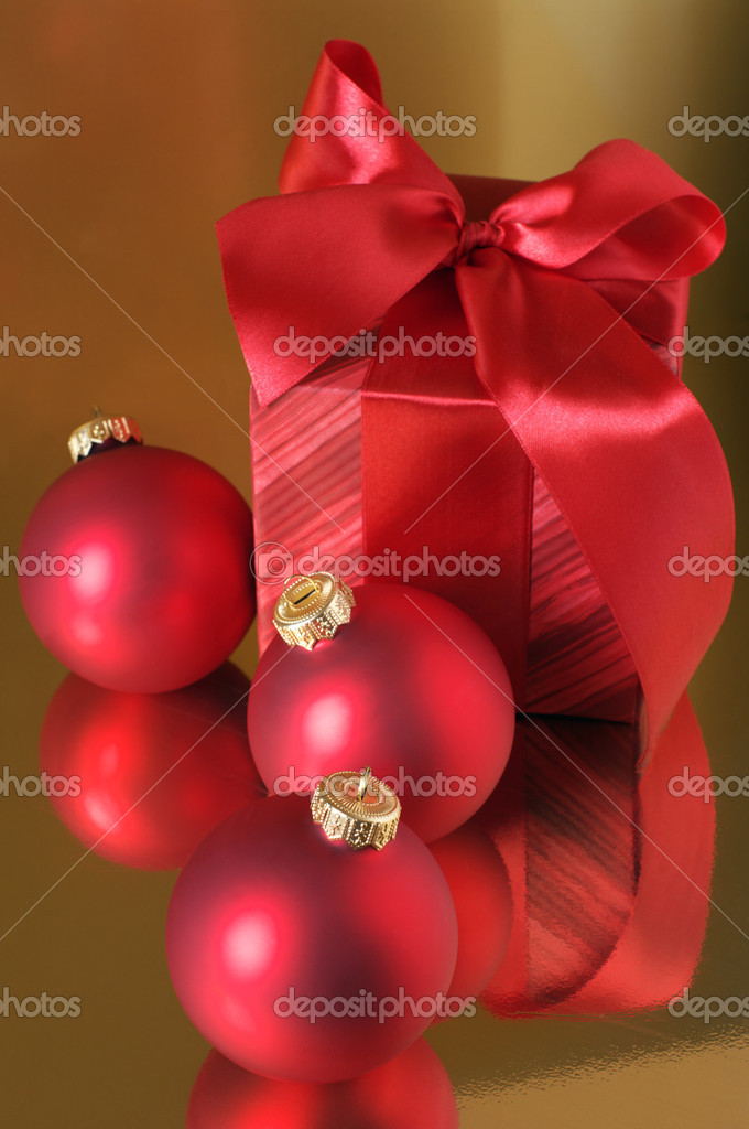 Red Christmas decorations and red gift on gold background. — Stock Photo #2847898