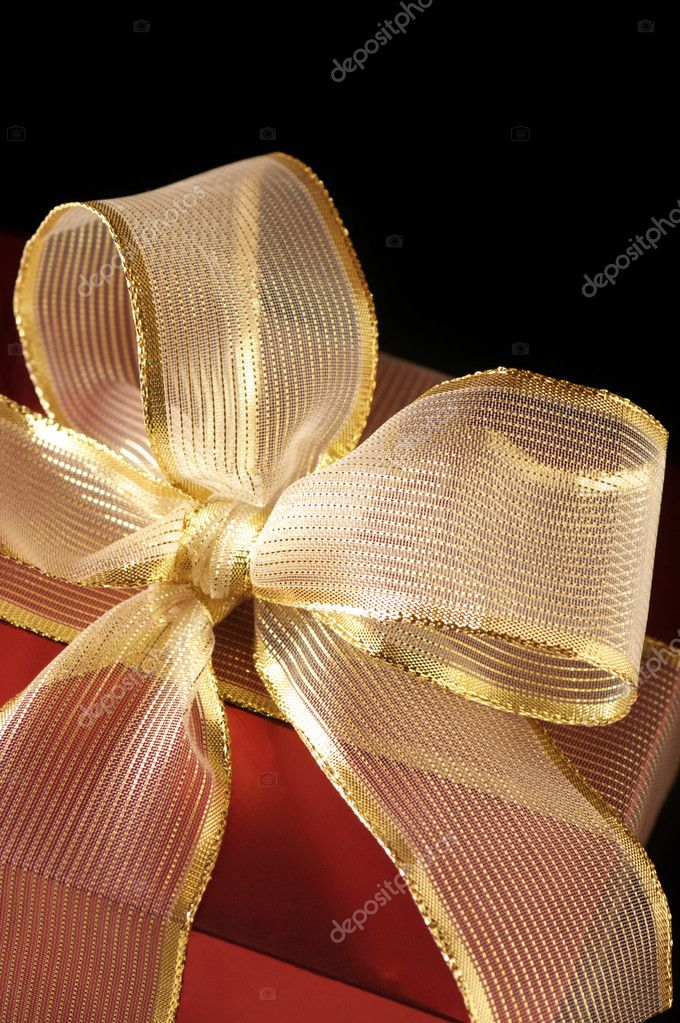Close-up of red foil gift with gold translucent bow on black background. — Stock Photo #2848315