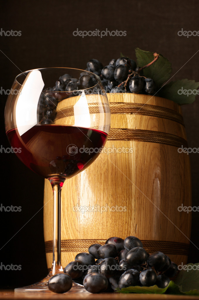 Glass of red wine, dark grape and souvenir barrel on wooden surface.  Stock Photo #2876663